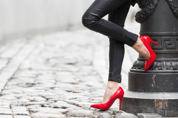 Women wearing black leather pants and red high heels