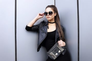 Photograph showing black choker, leather jacket, sunglasses, leather bag, black dress