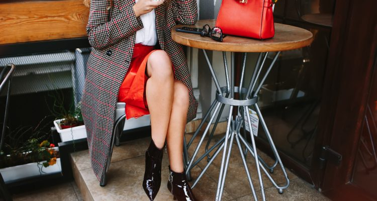 Women wearing red leather skirt and ankle boots with checked long coat. A coffee in her hand. Red hand bag