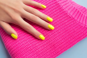 Pink knitted neon sweater with a woman's hand on it with yellow neon nail polish
