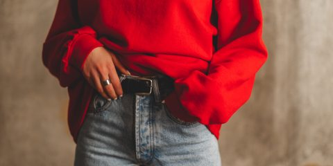 Women wearing red sweater with high waisted jeans and black belt