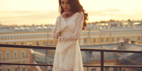 A women wearing white short lace dress with her hair open looking beautiful