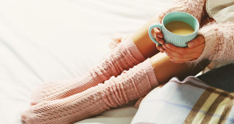 Women wearing pale pink warm knitted leg warmers and coffee cup. Warm sweater on