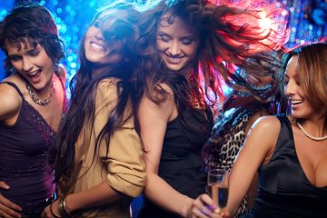 Young women having fun dancing at nightclub wearing fashionable clothing. 80s style