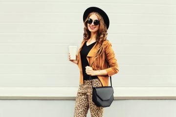 Fashion happy young smiling woman with coffee cup wearing a retro leopard leggings