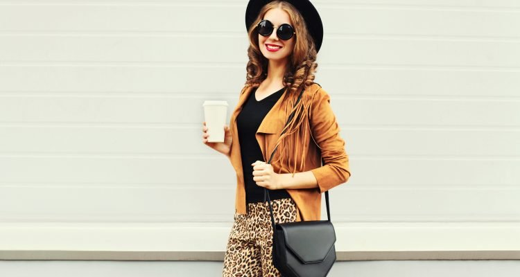 Fashion happy young smiling woman with coffee cup wearing a retro elegant hat, sunglasses, brown jacket and black handbag over grey background