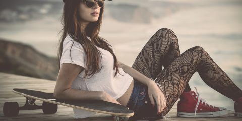 Beautiful and fashion young woman posing with a skateboard and converse's.