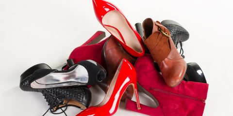 Bright red shoes lie on the heap. red shoes, black shoes and boots