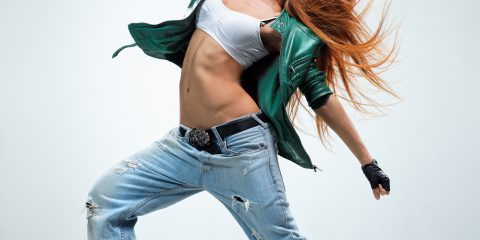 Women wearing hip-hop style clothing, green jacket, baggy jeans, white crop top and leather gloves