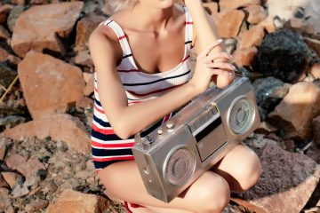 A girl on the beach wearing 80s swimming costume with retro radio and white sunglasses
