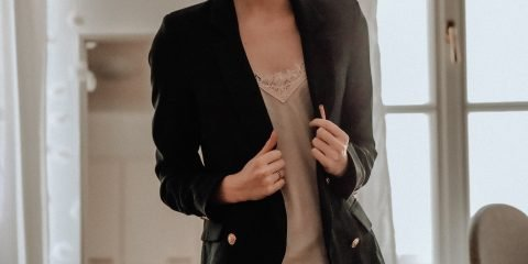 Women wearing black blazer with cream satin blouse
