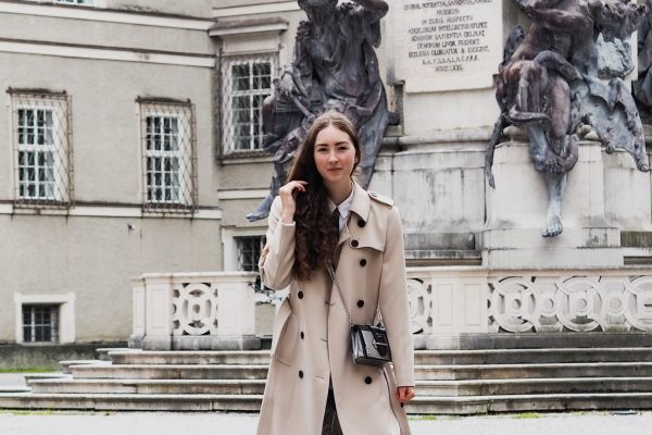 Women wearing a cream trench coat and ripped jeans