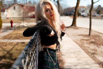 Women wearing plaid skirt with black crop top and red lipstick