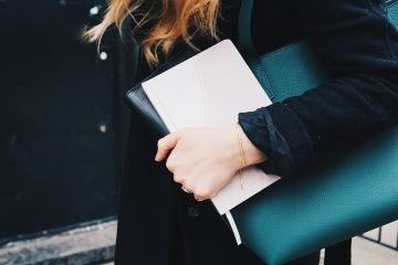 Women wearing smart clothes. Long black coat and black handbag going to work
