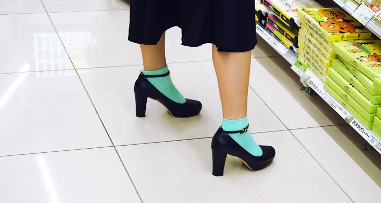 Women wearing mint colour socks with black shoes and black knee length skirt