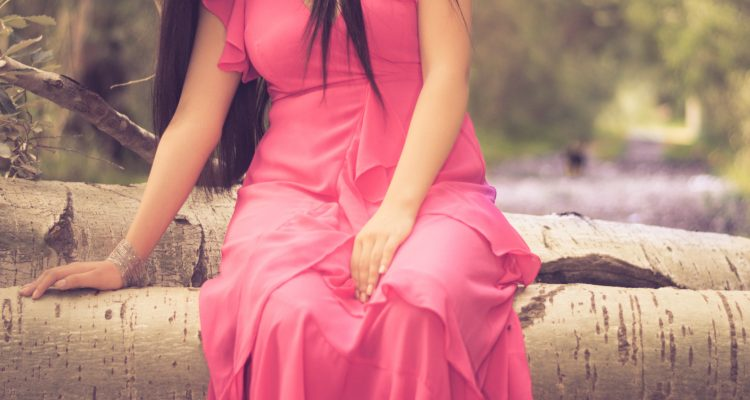 Women wearing a beautiful pink long sleeveless 80s inspired dress with earrings