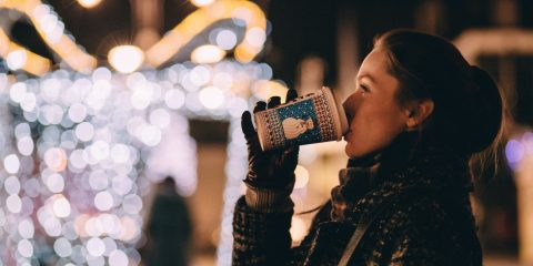 Women drinking hot chocolate with winter clothes and gloves