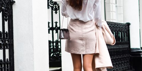 A women wearing cream mini skirt with white shirt and ankle boots