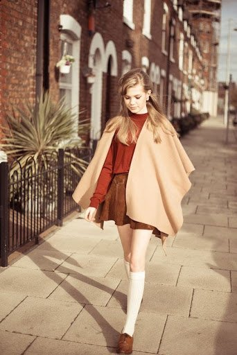 A Clothes Horse. Women wearing a cream poncho with a skater skirt