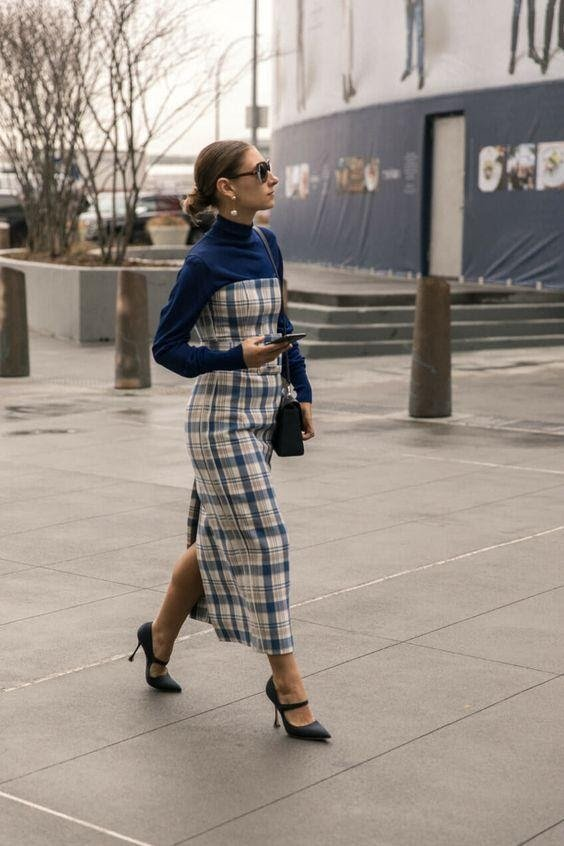 Women wearing a long plaid dress with slit at the back and retro sunglasses
