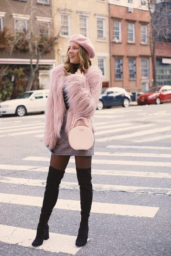 Women wearing a pink faux fur coat with knee high boots and mini skirt