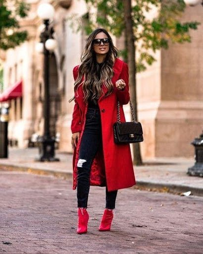 Women wearing long red winter coat with black skinny jeans and red ankle boots with black handbag