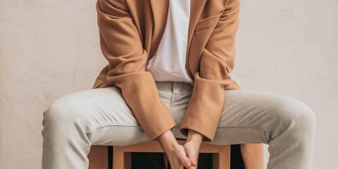 Man wearing eighties fashion clothing brown coat and white tee and jeans