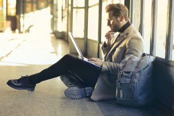 Man wearing a winter long coat in cream with laptop on his lap