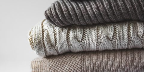 pile of grey winter warm sweaters