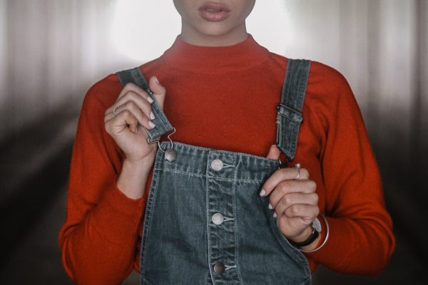 women wearing orange turtleneck and denim overall dress with hair up in a bun