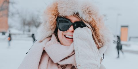 woman wearing parka coat in beige with sunglasses and gloves