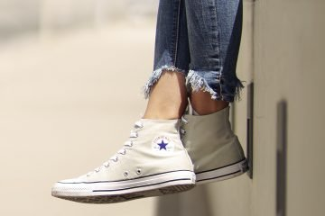 woman wearing white converse and ripped jeans