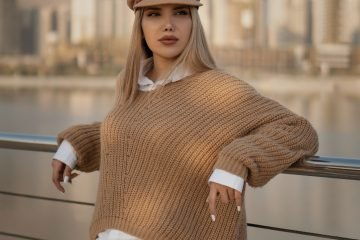 woman wearing a shirt and jumper on top with a hat and ripped jeans