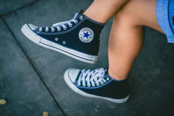 woman wearing black high top converse shoes with denim skirt