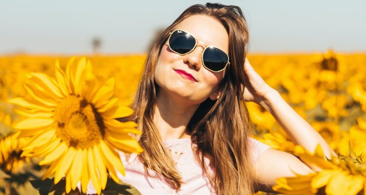 woman wearing sunglasses and denim jeans in a field of flowers