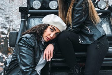 two women in leather jackets and ripped jeans sitting on a car