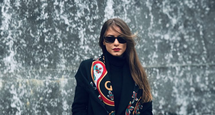 woman wearing a black coat with black sunglasses, red lipstick and scarf