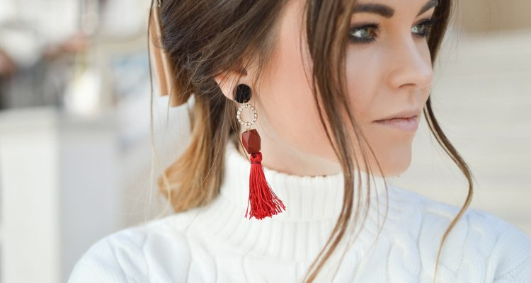 woman wearing statement earrings with white turtleneck