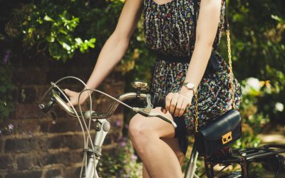 woman wearing a black summer dress and riding a bike with a hand bag