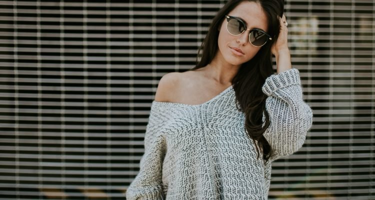 woman wearing black jeans and off the shoulder sweater with sunglasses