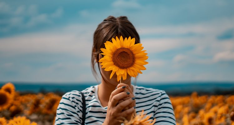 woman holding a flower and she is wearing a Breton top